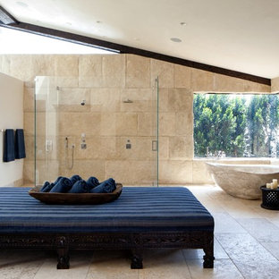 This is an example of a large mediterranean bathroom in Orange County with a freestanding tub, a curbless shower, beige tile, stone tile and beige walls.