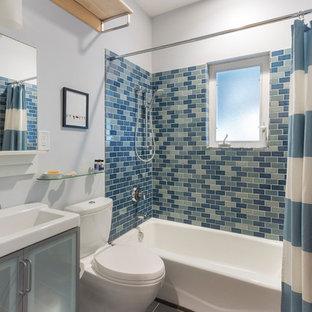 Новый формат декора квартиры: ванная комната в современном стиле с стеклянными фасадами, ванной в нише, душем над ванной, раздельным унитазом, синей плиткой, плиткой кабанчик, консольной раковиной, синими стенами и полом из сланца