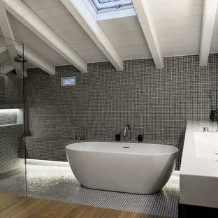 Inspiration for a large contemporary master bathroom in Other with an integrated sink, a freestanding tub, an open shower, a one-piece toilet, black walls, medium hardwood floors, black and white tile, ceramic tile, solid surface benchtops and an open shower.
