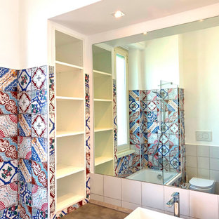 На фото: главная ванная комната с фиолетовыми фасадами, ванной в нише, биде, разноцветной плиткой, цементной плиткой, разноцветными стенами, полом из керамической плитки, настольной раковиной, красным полом и тумбой под одну раковину с