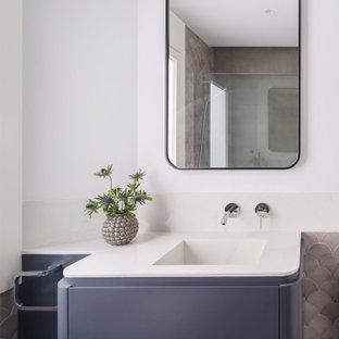 Modelo de cuarto de baño con ducha, contemporáneo, de tamaño medio, con baldosas y/o azulejos grises, baldosas y/o azulejos de cerámica, paredes blancas, suelo de baldosas de cerámica, lavabo integrado, encimera de cuarzo compacto, suelo gris, encimeras blancas, armarios con paneles lisos, puertas de armario grises, ducha a ras de suelo y ducha con puerta con bisagras