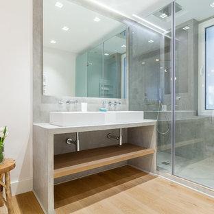 Diseño de cuarto de baño actual con armarios abiertos, paredes blancas, lavabo sobreencimera, ducha con puerta con bisagras, ducha empotrada, baldosas y/o azulejos grises, suelo de madera en tonos medios, suelo marrón y encimeras grises