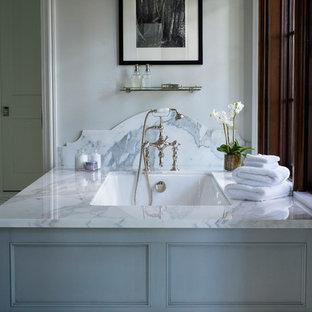 Foto di una grande stanza da bagno padronale classica con ante con riquadro incassato, ante grigie, top in marmo, vasca sottopiano, piastrelle a mosaico, pareti bianche e pavimento in marmo