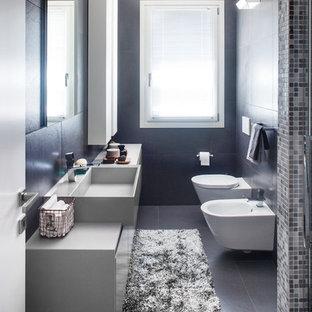 Modelo de cuarto de baño con ducha, contemporáneo, pequeño, con armarios con paneles lisos, lavabo de seno grande, puertas de armario grises, ducha a ras de suelo, sanitario de pared, baldosas y/o azulejos grises, baldosas y/o azulejos de porcelana, paredes grises, suelo de baldosas de porcelana, encimera de madera, suelo gris y ducha con puerta con bisagras