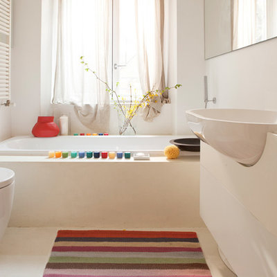 Small trendy drop-in bathtub photo in Milan with flat-panel cabinets, white cabinets, a one-piece toilet, white walls and a drop-in sink