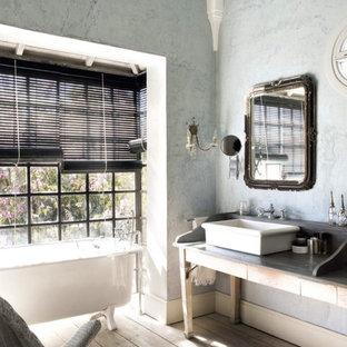 Modelo de cuarto de baño principal, romántico, de tamaño medio, con armarios abiertos, combinación de ducha y bañera, paredes multicolor, suelo de madera en tonos medios, lavabo sobreencimera y bañera con patas