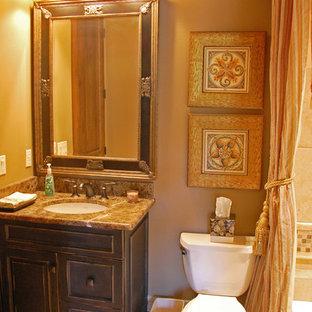 Imagen de cuarto de baño con ducha, mediterráneo, pequeño, con lavabo bajoencimera, bañera encastrada, combinación de ducha y bañera, sanitario de dos piezas, armarios tipo mueble, encimera de granito, baldosas y/o azulejos beige, baldosas y/o azulejos de cerámica, paredes marrones, suelo de baldosas de cerámica y puertas de armario de madera en tonos medios