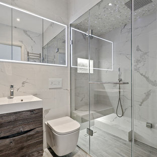 Photo of a small contemporary shower room bathroom in Surrey with flat-panel cabinets, dark wood cabinets, a built-in shower, a wall mounted toilet, grey tiles, white tiles, grey walls, grey floors, a console sink and a hinged door.
