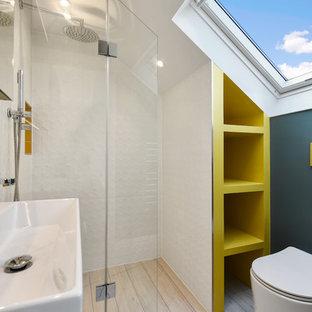 Aménagement d'une petit salle de bain contemporaine avec une douche d'angle, un carrelage jaune, un carrelage métro, un mur bleu, un lavabo suspendu, un sol beige et une cabine de douche à porte battante.
