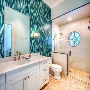 Modelo de cuarto de baño con ducha, marinero, de tamaño medio, con puertas de armario blancas, sanitario de dos piezas, paredes beige, lavabo bajoencimera, ducha con puerta con bisagras, encimeras blancas, armarios con paneles empotrados, ducha a ras de suelo, baldosas y/o azulejos azules y suelo beige