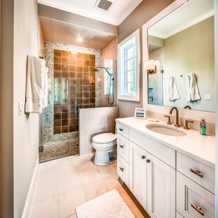 Inspiration for a mid-sized beach style 3/4 brown tile beige floor alcove shower remodel in Tampa with white cabinets, a two-piece toilet, beige walls, an undermount sink, a hinged shower door, white countertops and recessed-panel cabinets