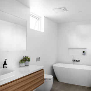 This is an example of a contemporary bathroom in Sunshine Coast with flat-panel cabinets, medium wood cabinets, a freestanding tub, white tile, mosaic tile, a drop-in sink, grey floor, white benchtops and a floating vanity.