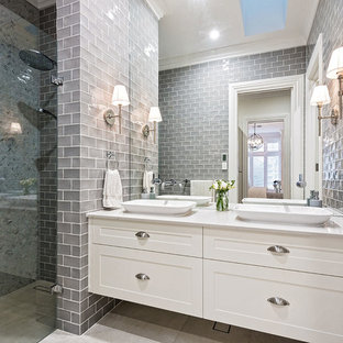 Design ideas for a large traditional 3/4 bathroom in Hobart with shaker cabinets, white cabinets, a freestanding tub, a double shower, a one-piece toilet, gray tile, subway tile, white walls, ceramic floors, a vessel sink, granite benchtops, white floor, a hinged shower door and white benchtops.