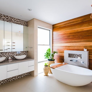 Photo of a contemporary bathroom in Gold Coast - Tweed with flat-panel cabinets, white cabinets, a freestanding tub, multi-coloured tile, mosaic tile, brown walls, a vessel sink, beige floor, grey benchtops, a niche, a double vanity, a floating vanity and wood walls.