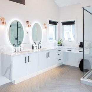Réalisation d'une très grande salle de bain principale minimaliste avec un placard à porte plane, des portes de placard blanches, une baignoire indépendante, une douche d'angle, un WC à poser, un carrelage blanc, des carreaux de céramique, un mur blanc, un sol en carrelage de porcelaine, un lavabo encastré, un plan de toilette en quartz modifié, un sol gris, une cabine de douche à porte battante et un plan de toilette blanc.