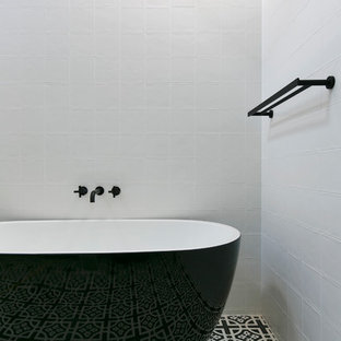 Design ideas for a contemporary master bathroom in Sydney with a freestanding tub, white walls and black floor.