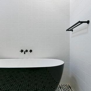 Idee per una stanza da bagno padronale contemporanea con vasca freestanding, pareti bianche e pavimento nero