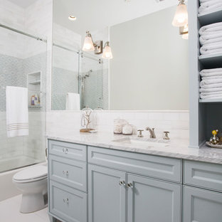 This is an example of a medium sized classic family bathroom in Austin with recessed-panel cabinets, grey cabinets, a shower/bath combination, white tiles, ceramic tiles, white walls, terracotta flooring, a submerged sink, marble worktops and grey floors.