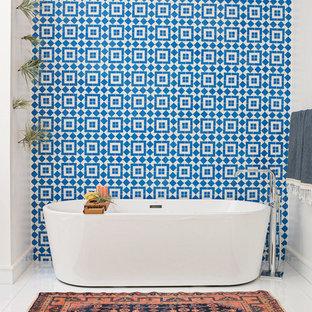 Diseño de cuarto de baño actual con bañera exenta, baldosas y/o azulejos azules, baldosas y/o azulejos blancos, paredes blancas y baldosas y/o azulejos de cemento