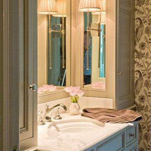 Exemple d'une petit salle d'eau chic avec un lavabo encastré, un placard avec porte à panneau encastré, des portes de placard grises, un plan de toilette en marbre et un mur multicolore.