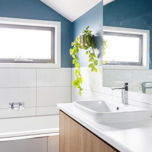 This is an example of a contemporary bathroom in Melbourne with flat-panel cabinets, medium wood cabinets, an alcove tub, white tile, blue walls, a drop-in sink, black floor, white benchtops, a floating vanity and vaulted.
