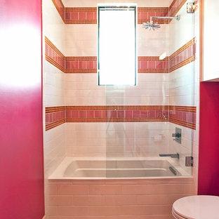 オースティンのトランジショナルスタイルのおしゃれな浴室 (アルコーブ型浴槽、シャワー付き浴槽、ピンクのタイル、ピンクの壁) の写真