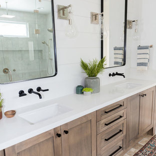Large country master wet room bathroom in San Diego with shaker cabinets, dark wood cabinets, gray tile, white walls, travertine floors, an undermount sink, quartzite benchtops, brown floor and a hinged shower door.