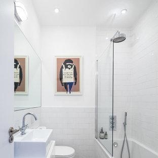 Idee per una stanza da bagno design con lavabo a bacinella, ante lisce, ante bianche, vasca da incasso, vasca/doccia, piastrelle bianche, piastrelle diamantate e pavimento multicolore