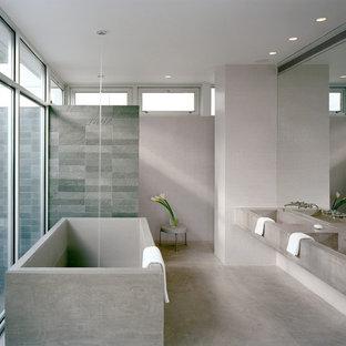 Imagen de cuarto de baño principal, minimalista, con bañera exenta, ducha a ras de suelo, suelo de cemento, lavabo integrado y encimera de cemento