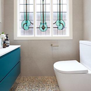 Idée de décoration pour une petit salle de bain principale design avec des portes de placards vertess, un combiné douche/baignoire, un WC suspendu, un carrelage beige, un sol en terrazzo, une cabine de douche à porte battante, un plan de toilette blanc, un placard en trompe-l'oeil, une baignoire posée, un carrelage de pierre, un mur beige, une vasque, un plan de toilette en quartz modifié et un sol multicolore.