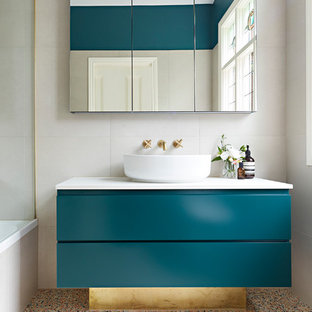 Small contemporary master bathroom in Melbourne with beige tile, beige walls, terrazzo floors, a vessel sink, multi-coloured floor, white benchtops, green cabinets, a shower/bathtub combo, a hinged shower door, furniture-like cabinets, a drop-in tub, a wall-mount toilet, stone tile and engineered quartz benchtops.