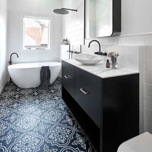 На фото: маленькая ванная комната в современном стиле с черными фасадами, отдельно стоящей ванной, душевой комнатой, инсталляцией, белой плиткой, плиткой кабанчик, белыми стенами, душевой кабиной, врезной раковиной, столешницей из ламината, разноцветным полом, открытым душем, белой столешницей, фасадами островного типа и полом из керамогранита с