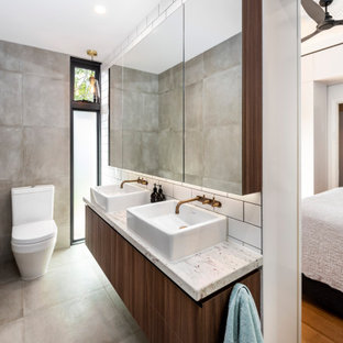 Mid-sized contemporary master bathroom in Melbourne with flat-panel cabinets, medium wood cabinets, a corner tub, an open shower, a two-piece toilet, gray tile, porcelain tile, grey walls, porcelain floors, a vessel sink, granite benchtops, grey floor, an open shower and white benchtops.