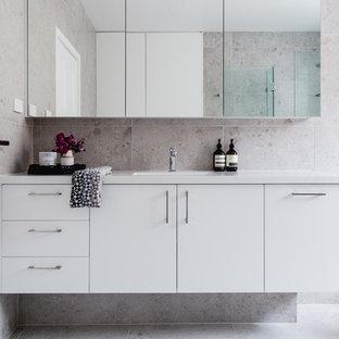 Idéer för att renovera ett mellanstort funkis en-suite badrum, med beige kakel, klinkergolv i keramik, släta luckor, vita skåp, beige väggar och ett integrerad handfat