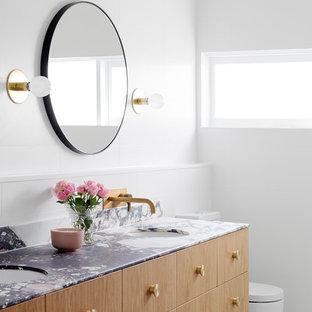 Foto di una grande stanza da bagno padronale design con ante lisce, ante in legno chiaro, vasca freestanding, doccia alcova, WC monopezzo, piastrelle di cemento, pavimento in cementine, lavabo integrato, top in marmo e pavimento nero