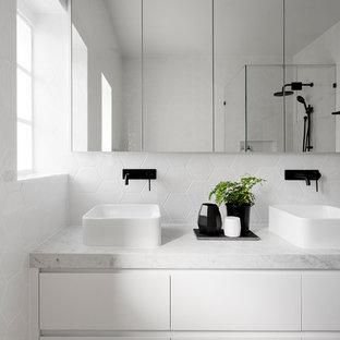 Свежая идея для дизайна: большая главная ванная комната в современном стиле с плоскими фасадами, белыми фасадами, накладной ванной, угловым душем, унитазом-моноблоком, белой плиткой, керамической плиткой, белыми стенами, полом из цементной плитки, настольной раковиной, мраморной столешницей, желтым полом и душем с распашными дверями - отличное фото интерьера