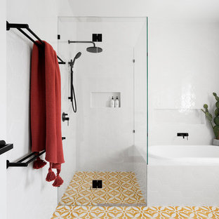 Inspiration for a mid-sized contemporary 3/4 white tile and porcelain tile yellow floor and cement tile floor bathroom remodel in Melbourne with a hinged shower door, flat-panel cabinets, white cabinets and white walls