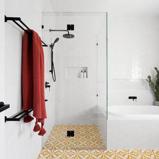 Пример оригинального дизайна: ванная комната среднего размера в современном стиле с накладной ванной, угловым душем, белой плиткой, душевой кабиной, желтым полом, душем с распашными дверями, керамогранитной плиткой, полом из цементной плитки, плоскими фасадами, белыми фасадами и белыми стенами
