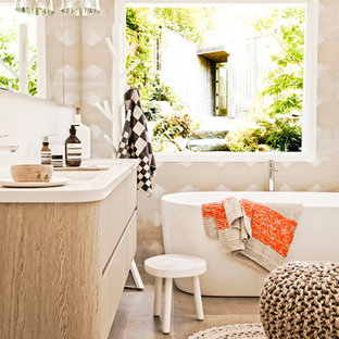 Mid-sized trendy freestanding bathtub photo in Melbourne with flat-panel cabinets and light wood cabinets