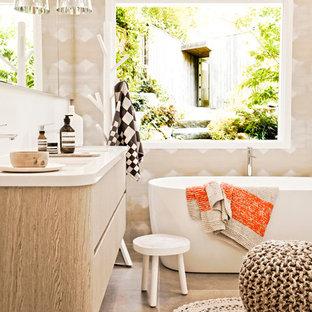 Idée de décoration pour une salle de bain design de taille moyenne avec un placard à porte plane, des portes de placard en bois clair et une baignoire indépendante.