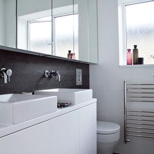 Esempio di una stanza da bagno per bambini contemporanea di medie dimensioni con ante lisce, ante bianche, WC sospeso, pistrelle in bianco e nero, piastrelle in ardesia, pareti bianche, pavimento con piastrelle in ceramica, lavabo rettangolare, top in superficie solida e pavimento nero