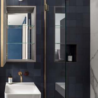 Photo of a contemporary ensuite bathroom in London with a walk-in shower, blue tiles, cement tiles, a wall-mounted sink, a hinged door, a single sink and a wall niche.