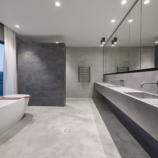 Inspiration for a large modern master bathroom in Perth with grey cabinets, a freestanding tub, gray tile, stone slab, grey walls, concrete floors, concrete benchtops, grey floor, an open shower, grey benchtops, a double vanity, a curbless shower, an integrated sink and a floating vanity.