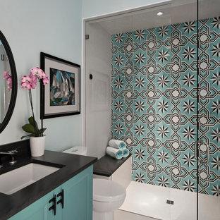 他の地域の中サイズのトランジショナルスタイルのおしゃれなバスルーム (浴槽なし) (シェーカースタイル扉のキャビネット、青いキャビネット、段差なし、マルチカラーのタイル、白い壁、アンダーカウンター洗面器、白い床、オープンシャワー、黒い洗面カウンター、分離型トイレ、セメントタイル、磁器タイルの床、御影石の洗面台) の写真
