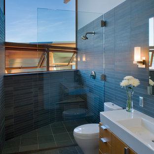 Ejemplo de cuarto de baño actual, grande, con lavabo integrado, armarios con paneles lisos, puertas de armario de madera oscura, ducha abierta, sanitario de una pieza, baldosas y/o azulejos negros y baldosas y/o azulejos de piedra