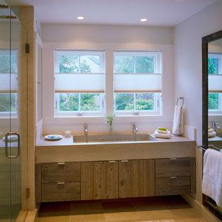 Modelo de cuarto de baño marinero con lavabo de seno grande, armarios con paneles lisos, encimera de cemento, ducha empotrada y paredes blancas