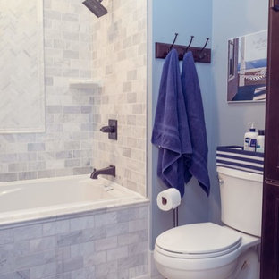 Bathroom - craftsman master white tile and marble tile porcelain floor and white floor bathroom idea in Cedar Rapids with recessed-panel cabinets, dark wood cabinets, a two-piece toilet, blue walls, an integrated sink, solid surface countertops and white countertops