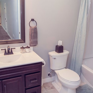 Arts and crafts marble tile porcelain floor and white floor bathroom photo in Cedar Rapids with recessed-panel cabinets, dark wood cabinets, a two-piece toilet, an integrated sink, solid surface countertops and white countertops