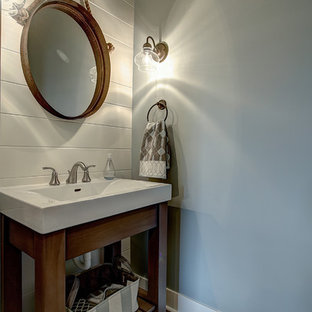 Idee per una piccola stanza da bagno con doccia american style con nessun'anta, ante in legno scuro, pareti blu, pavimento in legno massello medio, lavabo integrato, top in superficie solida e pavimento marrone