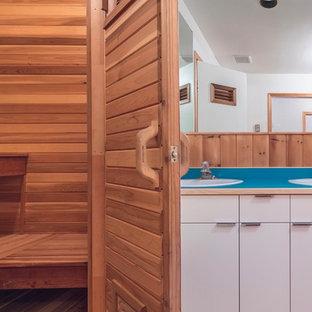 Foto di una sauna rustica di medie dimensioni con ante lisce, ante bianche, vasca ad alcova, vasca/doccia, pareti marroni, pavimento in legno massello medio, lavabo a consolle, top in laminato, pavimento marrone, doccia aperta e top blu